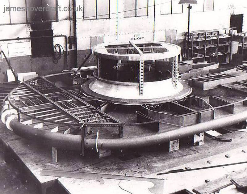 The SRN1 being manufactured - The shell of the SRN1 during construction. The engine mount and main intake is clearly visible as is the inner shell of the plenum chamber. The top criss-cross of beams is the start of the outer layer of the plenum which, when reaching the edges of the craft, deflected the air downwards creating the famous air cushion effect by Momentum Curtain (Peter Insole).
