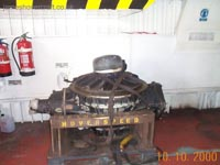 SRN4 systems tour - A gearbox being transported. Note its size compared to the two full-sized fire extinguishers. The input drive shaft to the gearbox would be connected to the left protrusion, the propeller shaft to the top (capped) and the lift fan to a protrusion on the bottom. An oil scavenge pump would be connected to the lowermost part of the flat plate on the right hand side, redistributing oil throughout the craft's systems.  (James Rowson).